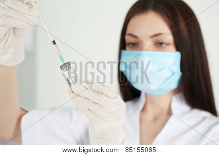 Ampule and syringe in hands of doctor