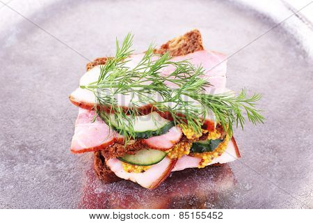 Delicious sandwich with ham, cucumber and mustard on metal tray, closeup