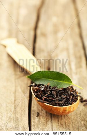 Black tea with leaf in spoon on old wooden table