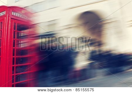 a defocused blur background of people walking in a street in London, United Kingdom, with a typical red telephone booth in the foreground