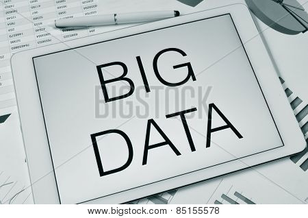 the text big data in the screen of a tablet on a table with charts and spreadsheet, in black and white