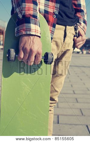 a young man with a plaid shirt holding a green skateboard in his hand
