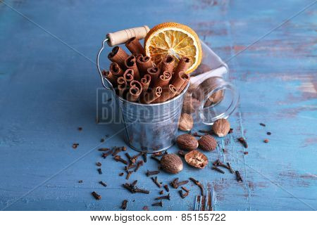 Cinnamon sticks with dried orange in metal bucket, nutmeg in glass jar and cloves on color wooden table background