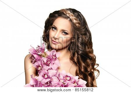 Beauty young woman, luxury long curly hair with orchid flower. Haircut. Beautiful girls fresh healthy skin, makeup, lips, eyelashes. Fashion model in spa care salon. Sexy trendy hairstyle look.