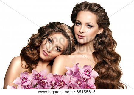 Two beauty young women, luxury long curly hair with orchid flower. Haircut. Beautiful girls fresh healthy skin, makeup, lips, eyelashes. Fashion models in spa care salon. Sexy trendy hairstyle look.