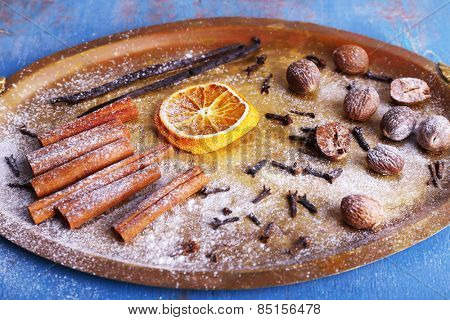 Cinnamon and vanilla sticks, dried orange, nutmeg and cloves on metal tray on color wooden background