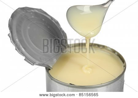 Tin can of condensed milk with spoon close up