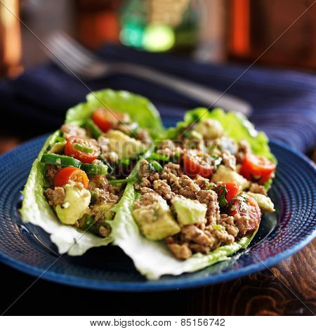 spicy avocado turkey lettuce wraps on blue plate