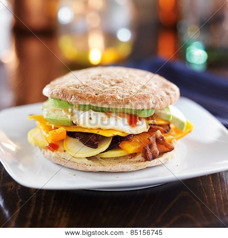 healthy breakfast sandwich with egg, bacon, avocado, hummus, and vegetables