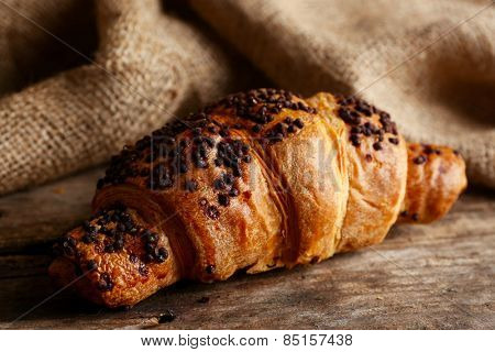 Fresh and tasty croissant with chocolate on wooden background