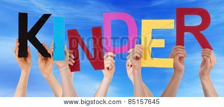 People Holding Colorful Word Kinder Means Kids Blue Sky