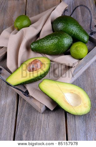 Avocado with limes on tray on wooden background