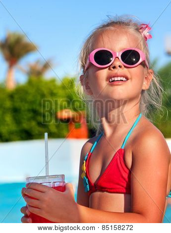 Child drinking soft drink near swimming pool. Look up.