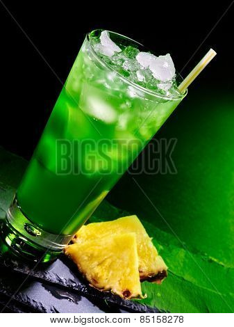 Green pineapplee drink  with ice cube on dark background.
