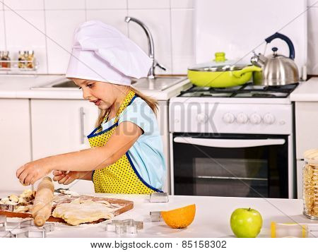 Child girl knead dough at kitchen.