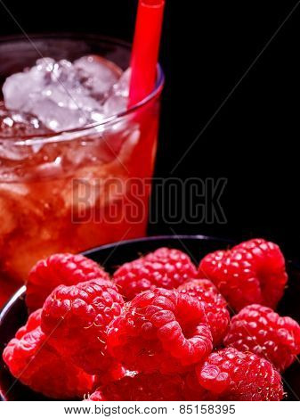 Red berry and cold drink  with cube ice on dark background. Top view.