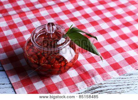 Jar of goji berry jam on napkin on table close up