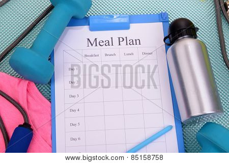 Meal plan and sports equipment top view close-up