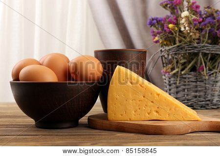 Tasty dairy products with bread and dry flowers on table on fabric background