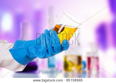 Hand holding chemical liquid in glass flask in laboratory