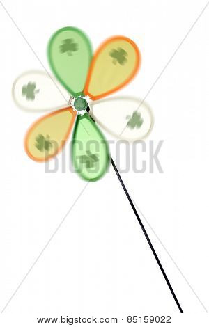 A spinning green, orange and white Irish pinwheel with a shamrock on each blade.  Isolated on white.