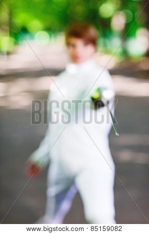 Tip of rapier held by fencer woman staying in park alley, shallow depth of field
