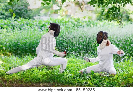 Two rapier fencer women fighting over beautiful nature park background
