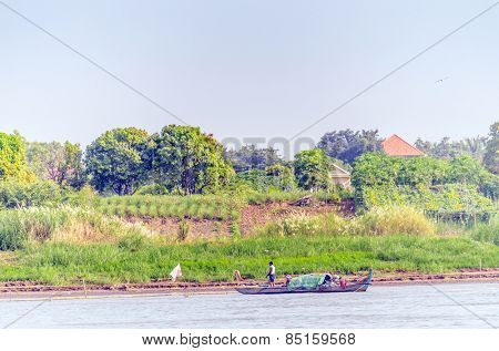 PHNOM PENH, CAMBODIA, JANUARY 2, 2013: Local people travel on fishing boat on Mekong river