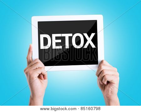 Tablet pc with text Detox with blue background
