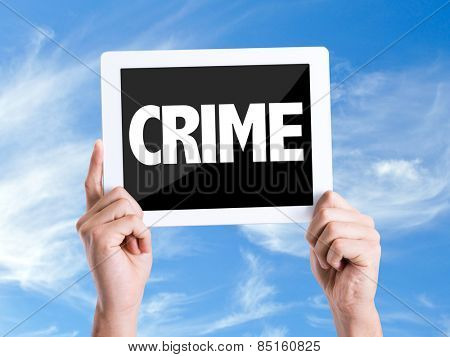 Tablet pc with text Crime with sky background