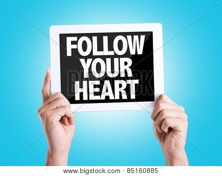 Tablet pc with text Follow Your Heart with blue background