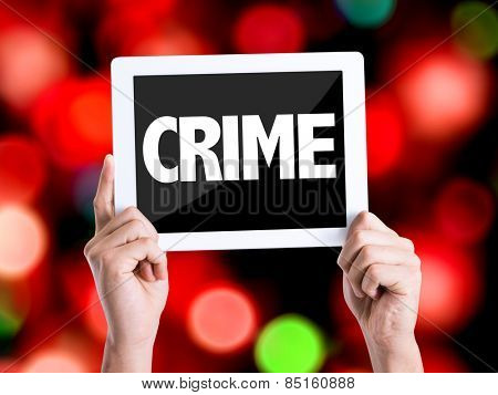 Tablet pc with text Crime with bokeh background