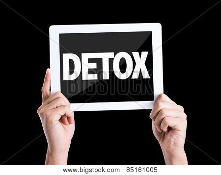 Tablet pc with text Detox isolated on black background