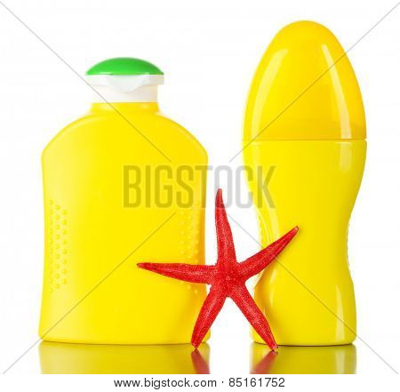 Bottles of suntan cream with sea star isolated on white