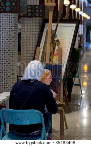 DOHA, QATAR - MARCH 8, 2015: A painter at work in the Souq Waqif Arts Centre