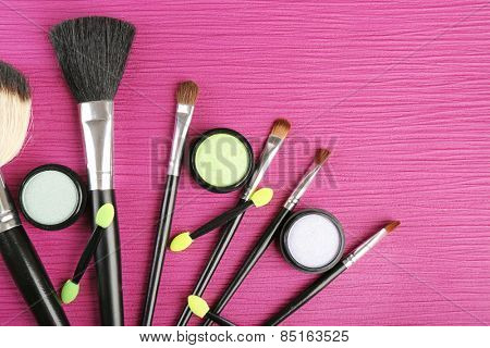 Set of makeup brushes on pink wooden table background