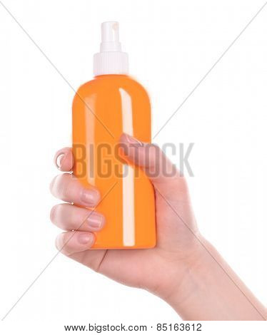 Bottle of suntan spray in female hand isolated on white