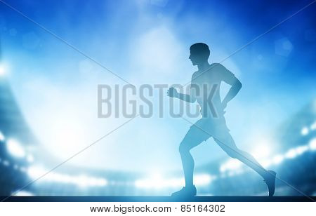 Man running on the stadium in night lights. Athletics run concept.