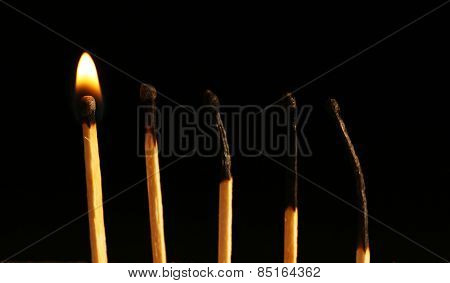 Burnt and burning matches on black background