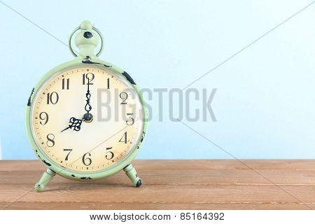 Alarm clock on wooden table on light background