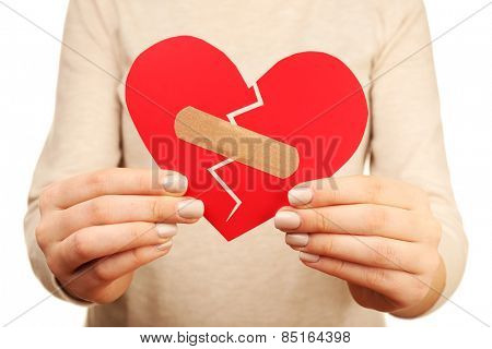Woman holding broken heart with plaster close up