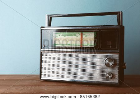 Retro radio on wooden table on color background
