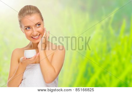 Young girl applying body cream isolated