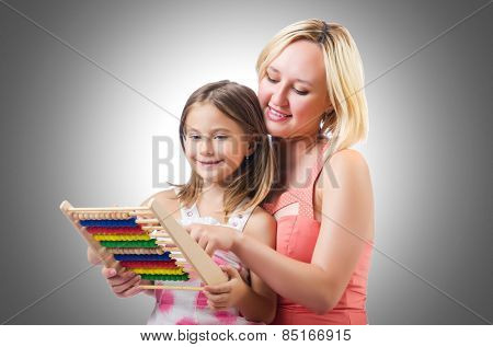 Mother and daughter with abacus on white