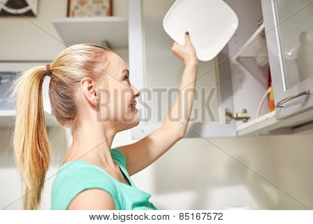 people, housework and housekeeping concept - happy woman putting plate to kitchen cabinet