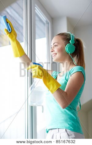 people, housework and housekeeping concept - happy woman in headphones listening to music and cleaning window with cleanser at home