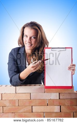 Woman builder and brick wall