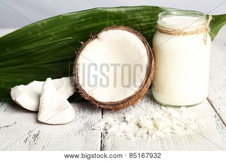 Fresh coconut oil in glass bottle and green leaf on color wooden table background