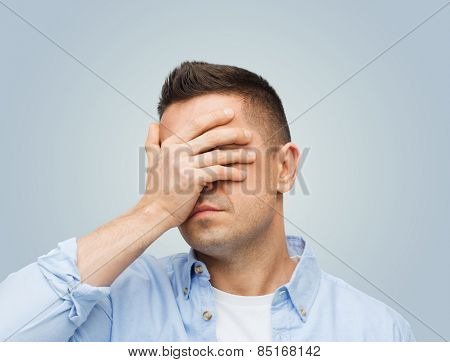 stress, headache, health care and people concept - unhappy man covering his eyes by hand over gray background