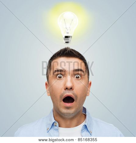 fear, emotions, horror, idea and people concept - scared man with big eyes and open mouth over gray background with lighting bulb
